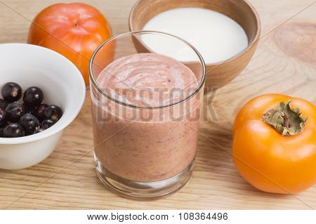 Glass Of Persimmon Smoothie With Blackcurrant And Milk, Decorated By Ingredients On Rustic Wooden