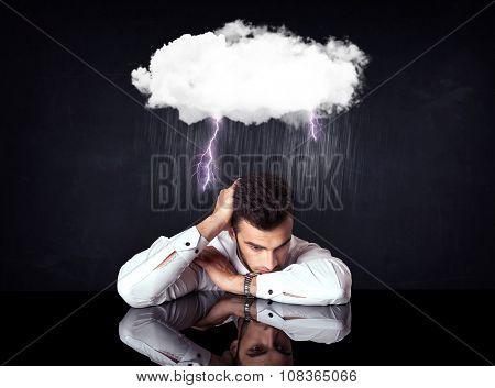 Depressed businessman sitting under a lightning rainy cloud