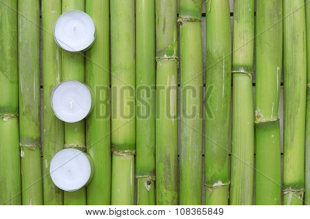Inspirational zen background. Three candles aligned on a natural green bamboo