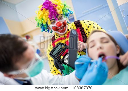 Crazy colorful clown with chainsaw in dental office