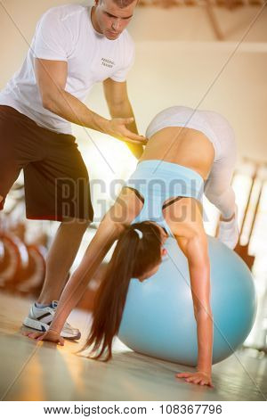 Attractive women exercise on the ball in the gym with the help of personal instructors