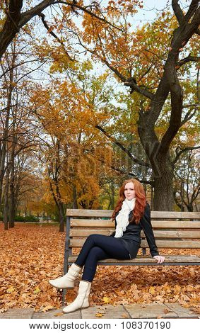 redhead girl sitting on a bench in city park, autumn season