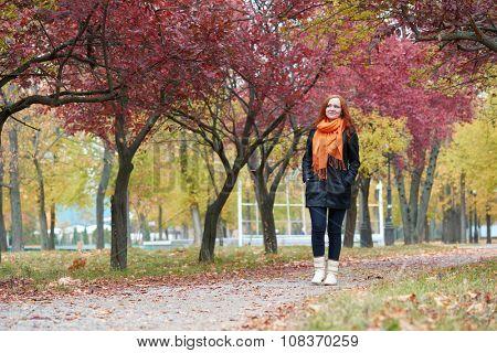 redhead girl walk on pathway in city park, fall season