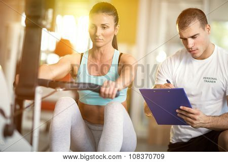 Gym woman and her trainer doing exercise at the gym.