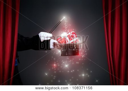 Magician hand with magic wand making Christmas  gift, Christmas spell