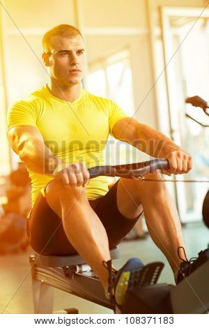 Young man in health club exercise on row machine