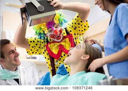 Funny clown in colorful clown suit make laugh young girl in dental office