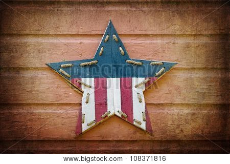 Retro style wooden star, decorated with the stars and stripes flag of the United States, over timber panel wall. Textured and with added vignette.