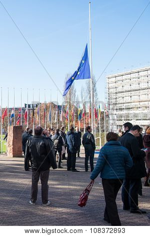STRASBOURG FRANCE - NOV 16 2015: Council of Europe employees under half-mast flags at the COE building for the minute of silence in tribute to the victims of the attacks in Paris which left at least 129 people dead