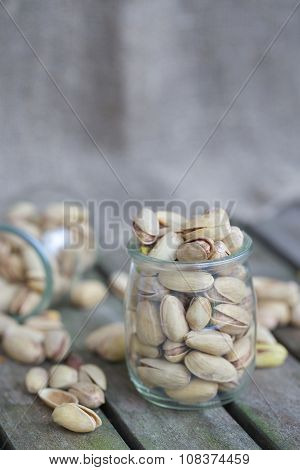 Pistachios in a glass on an old wooden surface. Closeup