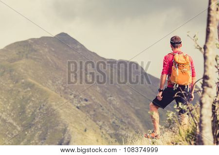 Hiking Man With Backpack In Mountains