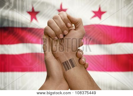Barcode Id Number On Wrist Of Dark Skinned Person And Usa States Flags On Background - District Of C