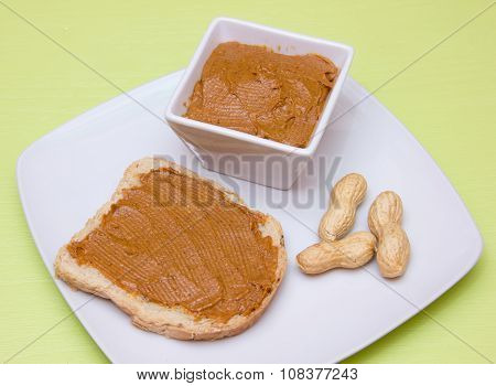 Slice of bread with peanut butter on green
