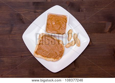 Slice of bread with peanut butter on wood from above