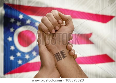 Barcode Id Number On Wrist Of Dark Skinned Person And Usa States Flags On Background - Ohio