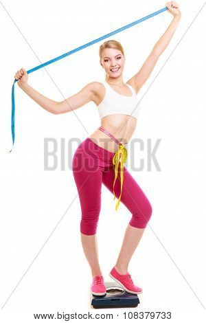 Woman Measuring On Weighing Scale With Raised Arms