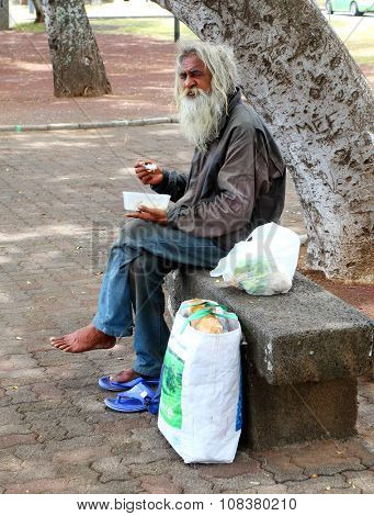 SAINT DENIS, REUNION ISLAND, FRANCE - NOVEMBER 3, 2015: Unidentified creole homeless man eating his lunch on a bench in park. Poor people on Reunion Island.