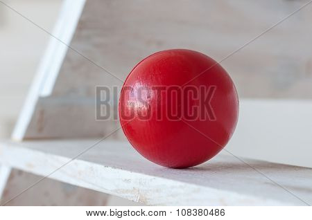Traditional children's games. Air-filled, elastic red ball, decorative, on white wooden stairs. With
