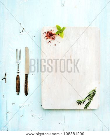 Kitchen-ware set. White wooden chopping board, knife, fork, spices and herbs on a light blue backgro