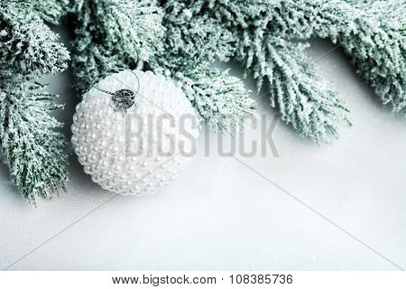 branch of Christmas tree with snow and ball