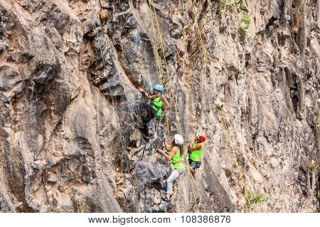 Group Of Courageous Climbers Climbing A Rock Wall