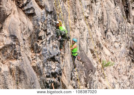Group Of Two Climbers Climbing A Rock Wall