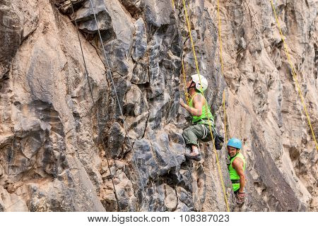 Group Of Climbers Climbing A Rock Wall