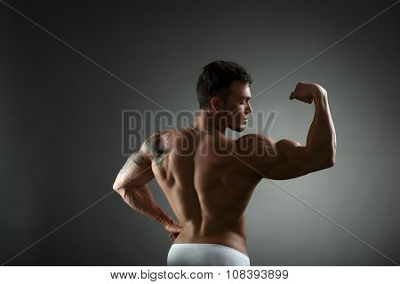 Rear view of tattooed bodybuilder showing biceps