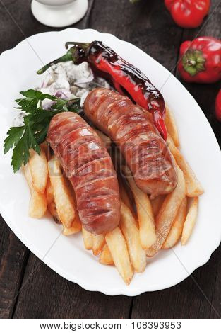 Grilled german sausages with french fries and roasted pepper