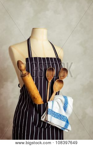 Apron on mannequin with baking utensils and cloth in pocket