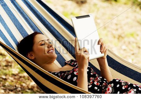 Woman Relaxing In Hammock With  Tablet computer