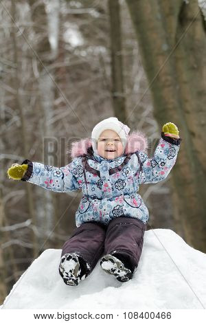 Laughing preschooler girl wearing warm clothing having fun on snowy hill in winter forest