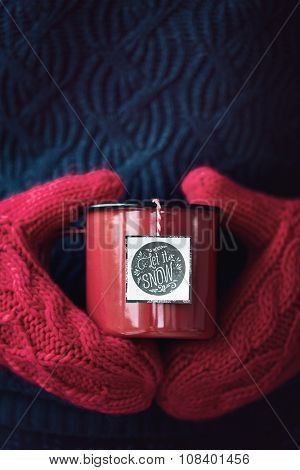 Mug of tea held in woollen mittens