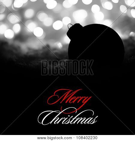 Mysterious Christmas Decoration with Black Ball in the Snow on the Background of White Blurred Holiday Lights. Greeting Card with Space for Your Text