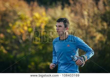 young athlete running in autumn forest
