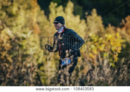 young smiling man running in autumn forest