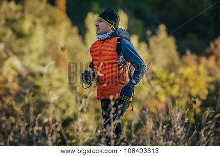 elegant young male runner running. background of autumn landscape