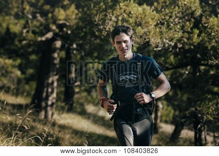 happy young male runner running through forest