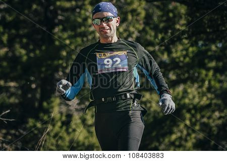 young smiling man with glasses runner is running through woods