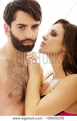 Beautiful topless woman whispering to shirtless man's ear.