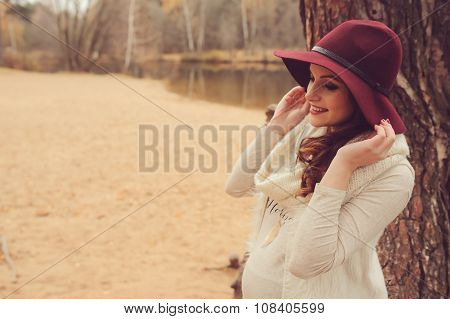 adorable pregnant woman in fashion hat on warm cozy outdoor walk