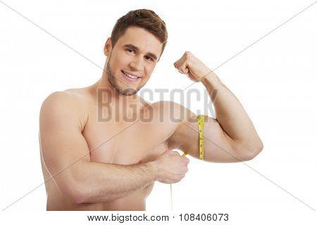 Handsome muscular man measuring his biceps.