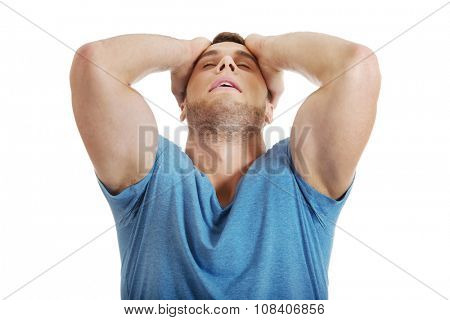 Handsome depressed man with hands behind head.
