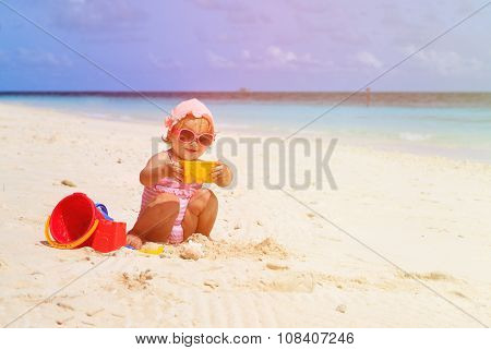 cute little girl building sandcastle on beach