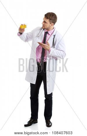 Male doctor or pharmacist presenting pills.