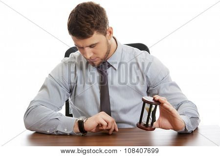 Businessman holding hourglass an checking time on his watch.