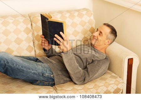 Relaxed mature man reading a book in living room.