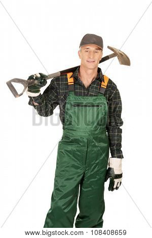 Smiling experienced gardener with a spade on shoulder