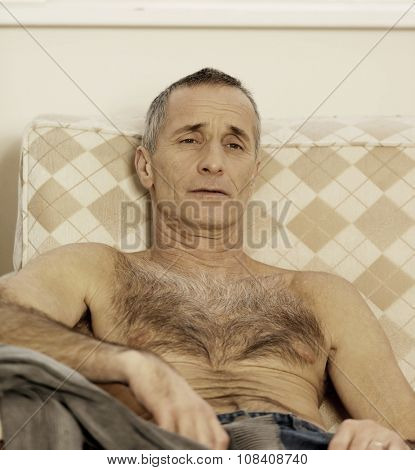 Shirtless handsome man sitting on a sofa.