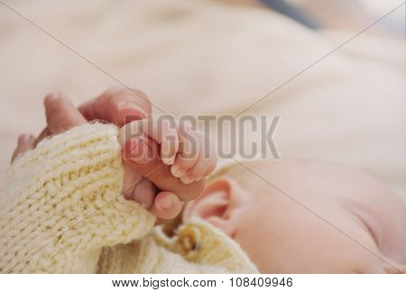 Close Up Mother's Hand Holding Little Hand Of Her Baby